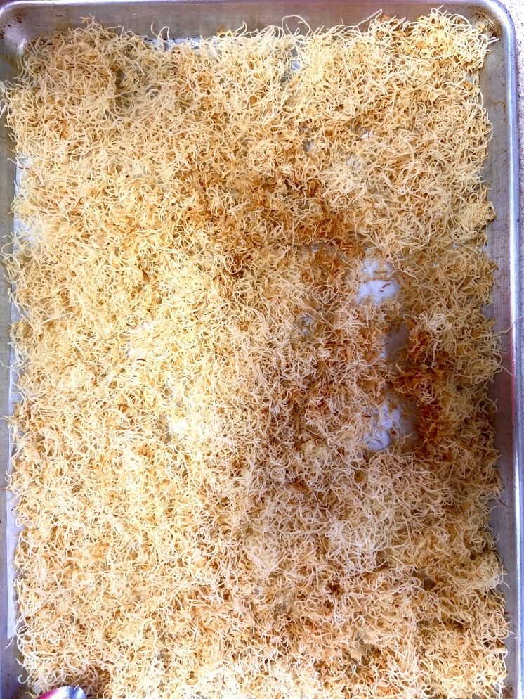 Spread the Kunafe-coconut oil-sugar mixture on a baking sheet and bake until it is golden brown and crunchy.